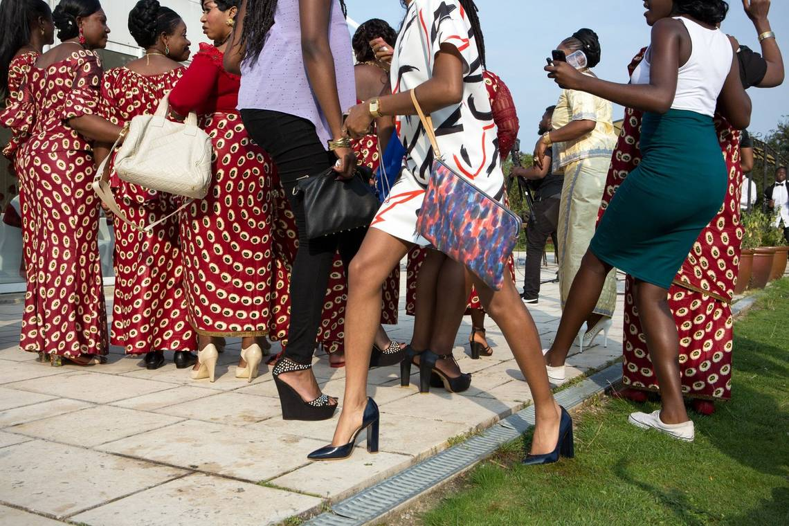 Women in modern European clothing walking in front of a group of women in traditional African dress in this photo by Carolina Arantes.