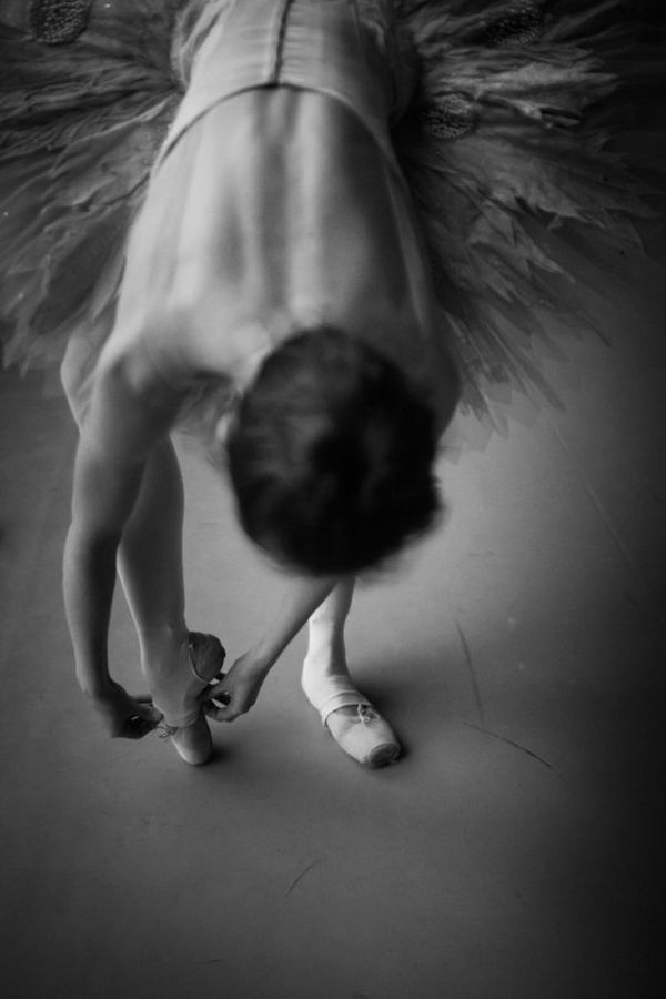 A black and white portrait of a ballerina tying her shoes. Photo by Clive Booth on a Canon EOS-1DX Mark II.