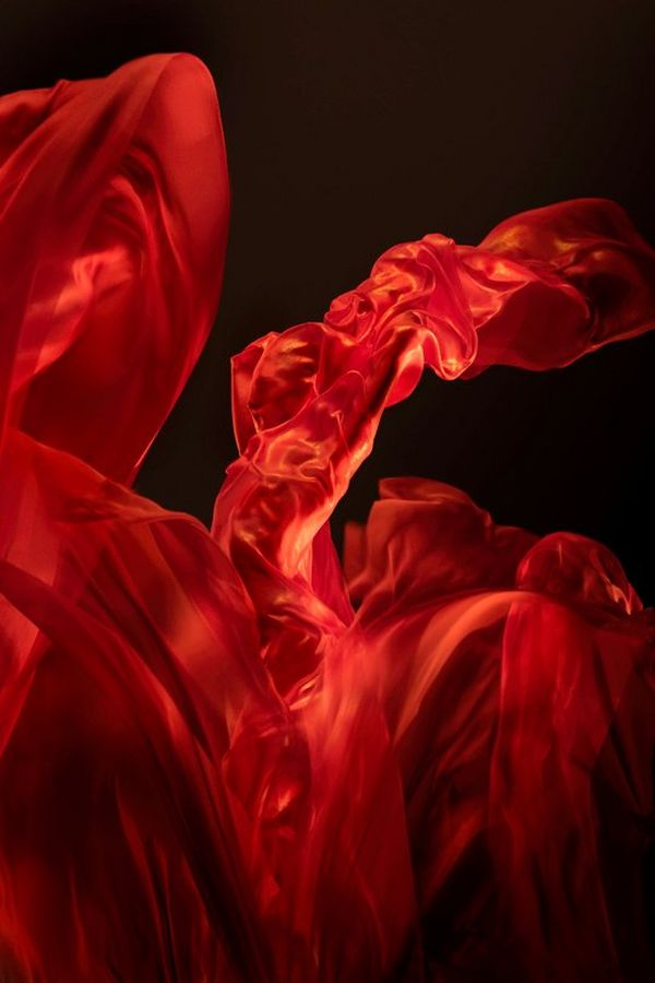 A dancer draped in red material, billowing like a flame. Photo by Clive Booth on a Canon EOS R.