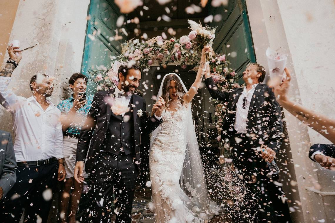 A newly married couple leave a church and are showered in confetti in Corsica. Taken by Canon Ambassador Félicia Sisco on a Canon EOS-1D X Mark II.