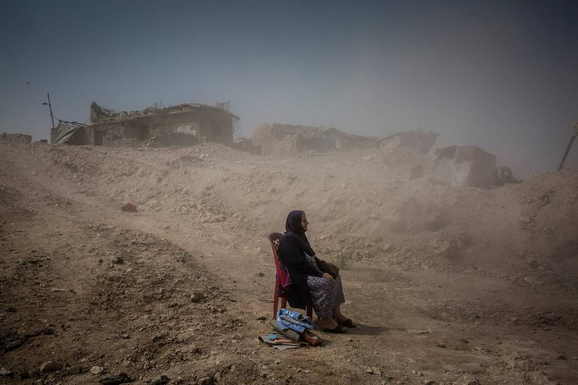 A woman sits in the rubble in the aftermath of the Battle of Mosul in 2017, by Canon Ambassador Ivor Prickett on a Canon EOS 5D Mark III.