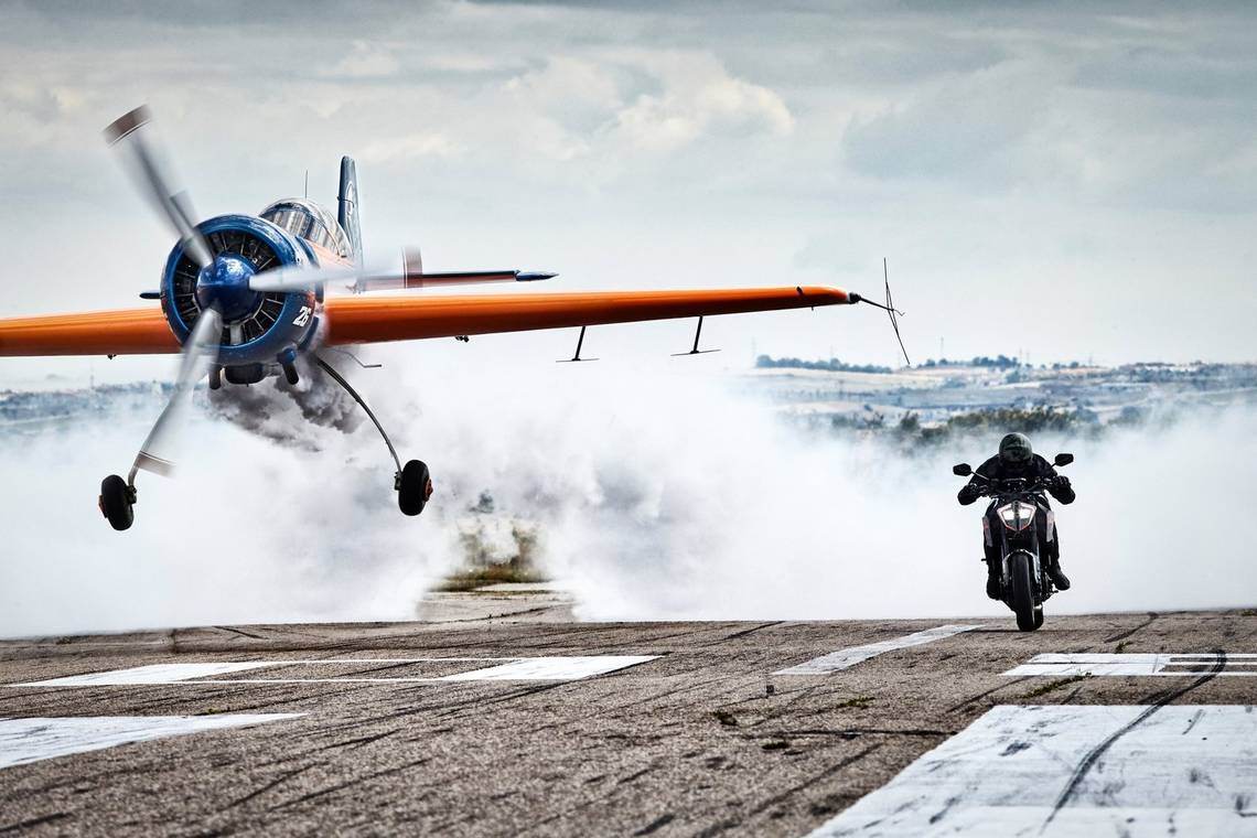 A stunt plane and a motorbike race towards the camera on a runway in Casarrubios, Spain, taken by Canon Ambassador Jaime de Diego on a Canon EOS-1D X.