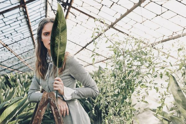 A woman stands in a greenhouse peering out from behind a large leaf. Taken by Jaroslav Monchak on a Canon EOS 5DS R.