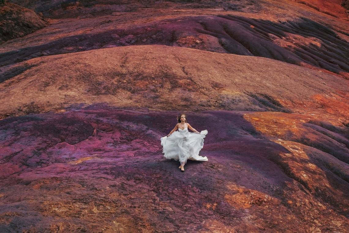 A woman in a white dress runs across purple and orange volcanic rock on the island of Mauritius. Photo taken by Katya Mukhina on a Canon EOS-1D X.