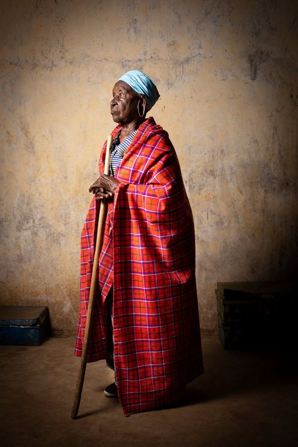 An 95-year-old Kenyan lady leans on a walking stick while gazing into the distance, taken by Lieve Blancquaert on a Canon EOS R.