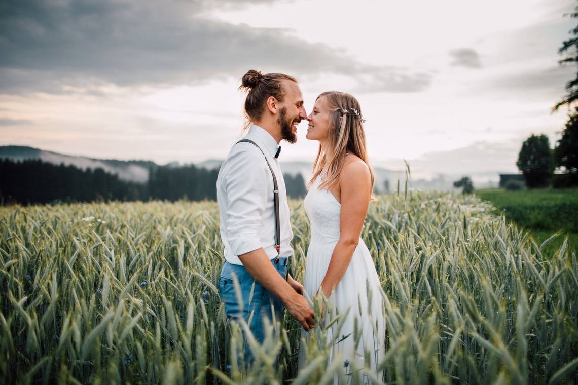 A happy newly-married couple in a field together, photographed by Markus Morawetz on a Canon EOS 5D Mark IV.