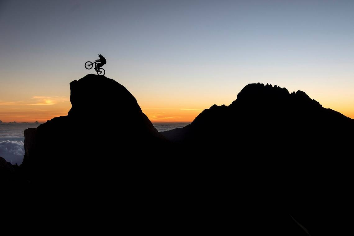 Silhouetted against the sunset, YouTube star and Red Bull rider Danny MacAskill hops on the back wheel of his mountain bike at the base camp of Mount Kilimanjaro. Taken by Canon Ambassador Martin Bissig on a Canon EOS 5D Mark IV.