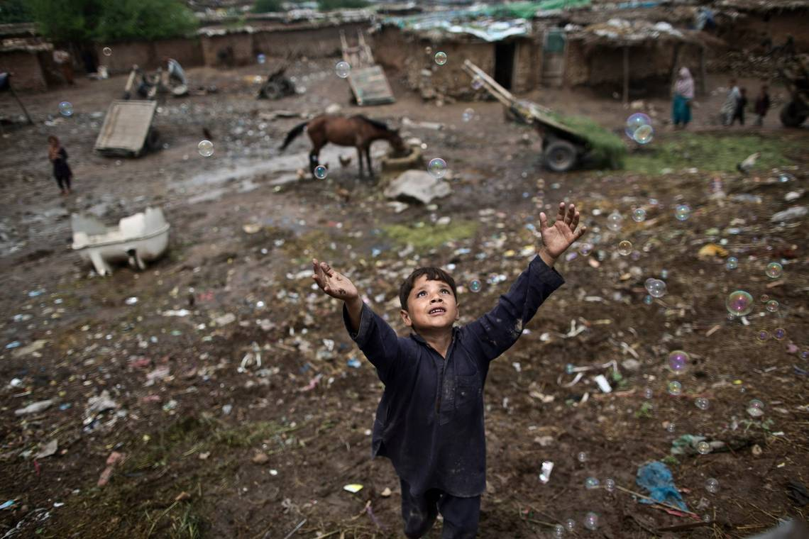 A young Afghan refugee boy jumps to catch a bubble in a poor part of Islamabad, photographed by Muhammed Muheisen on a Canon EOS 5D Mark III.