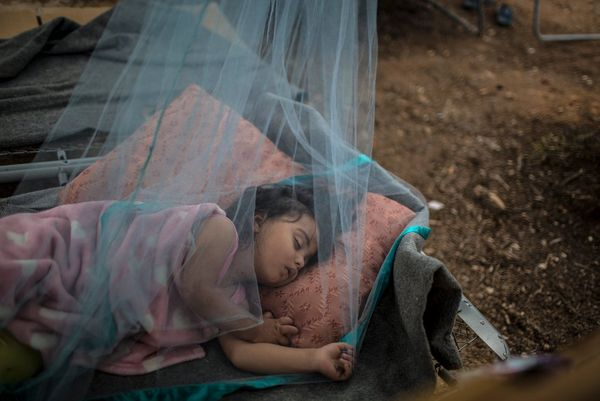 In a refugee camp north of Athens, a young refugee girl sleeps outside under a mosquito net to escape the heat in her family's tent, photographed by Muhammed Muheisen on a Canon EOS 5D Mark III.