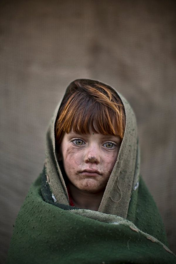 A six-year-old Afghan refugee near her family's mud home on the outskirts of Islamabad, Pakistan, photographed by Muhammed Muheisen on a Canon EOS 5D Mark III.