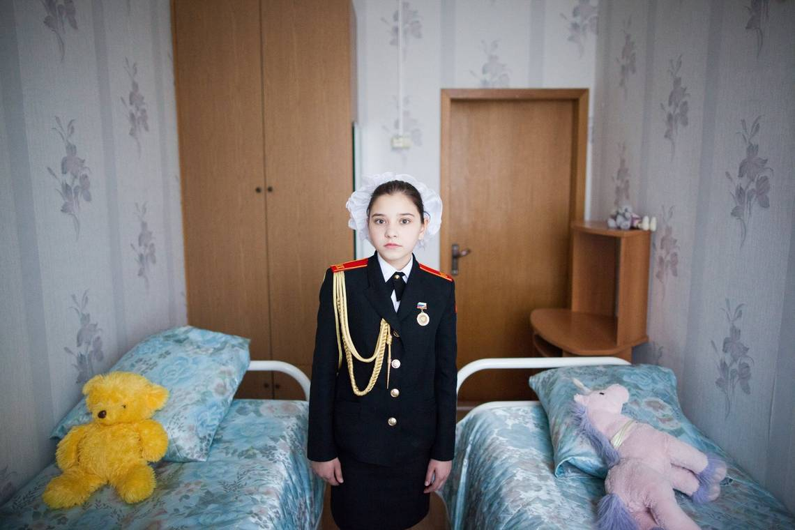 A Russian girl in her cadet school uniform stands in her bedroom, photographed by Pavel Volkov on a Canon EOS 5D Mark II.
