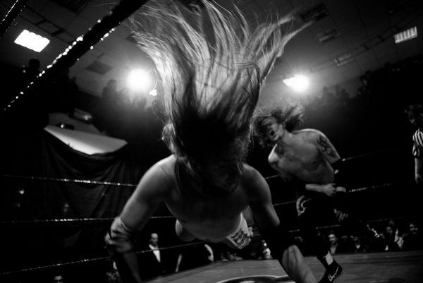 A long-haired wrestler is thrown to the floor by his opponent during a show at the Moscow Wrestling Club, photographed by Pavel Volkov on a Canon EOS 5D Mark II.