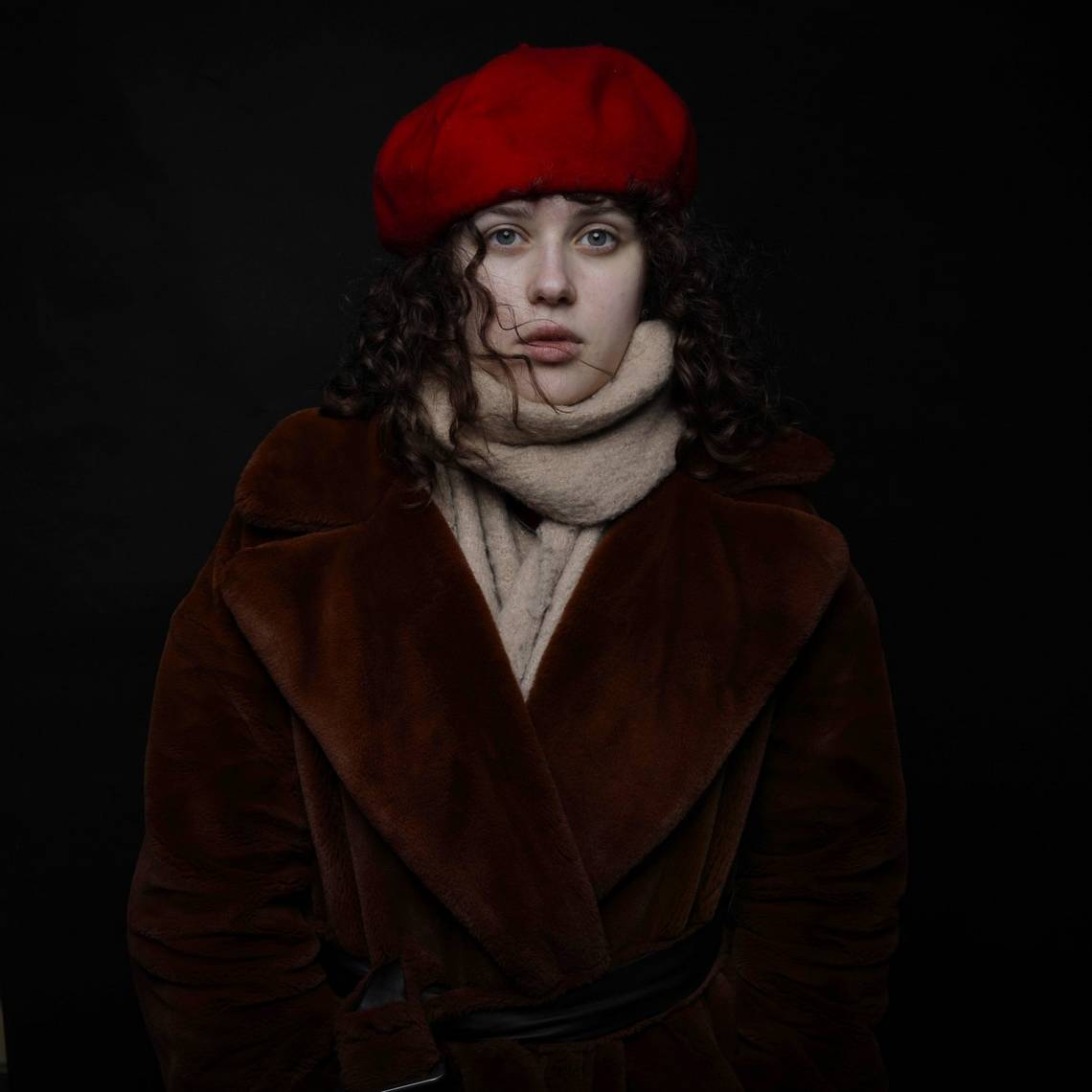 A woman stands against a black background wearing a winter coat and scarf, and a red beret. Taken by Canon Ambassador Piotr Małecki on a Canon EOS 5D Mark IV.