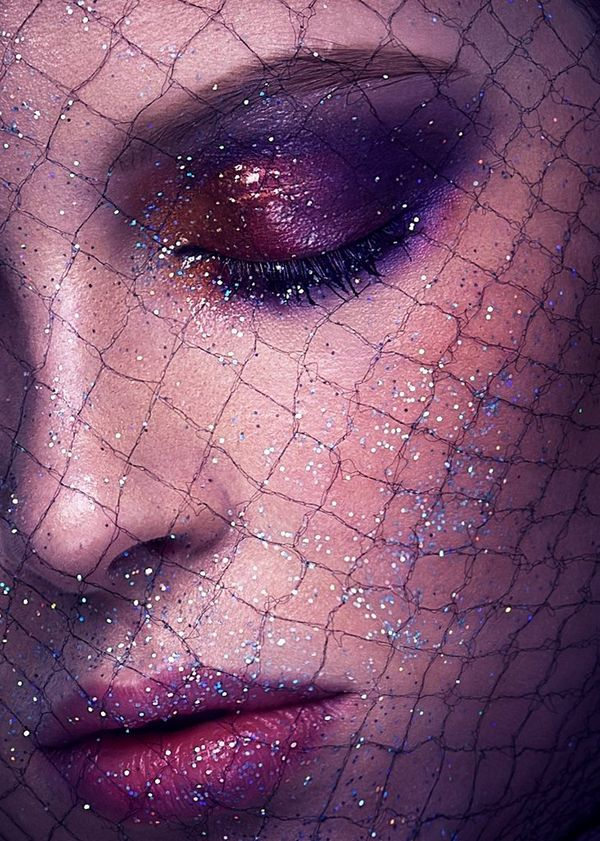 A close up of a woman's face, with bold purple makeup and glitter, and fishnet fabric on her face. Taken on a Canon EOS-1D X by Canon Ambassador Quentin Caffier.