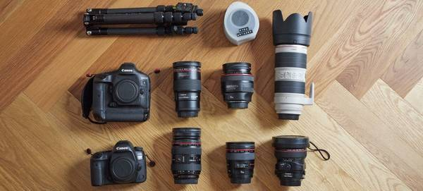 The contents of Quentin Caffier's photography kitbag are laid out: two Canon cameras, lenses, a tripod and filters.