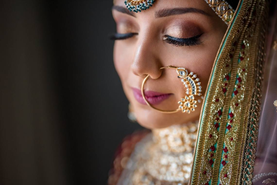 An Indian woman in silk wedding clothes and opulent gold jewellery turns towards the camera with her eyes closed. Taken by Canon Ambassador Sanjay Jogia on a Canon EOS R.