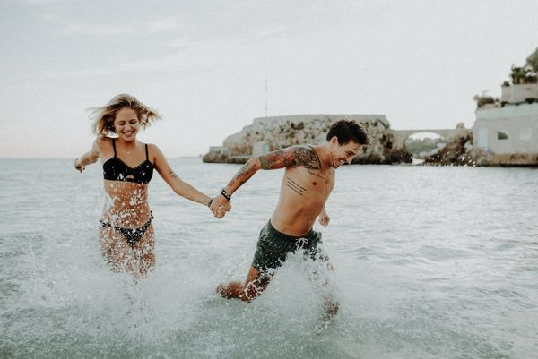 A couple running in the sea, photographed by Canon Ambassadors Julia Blumenthal and Gil Gropengießer on a Canon EOS 5D Mark III.