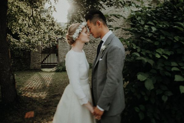 A newly married couple stand face-to-face, holding hands in a leafy churchyard. Photographed by Canon Ambassadors Julia Blumenthal and Gil Gropengießer on a Canon EOS 5D Mark IV.