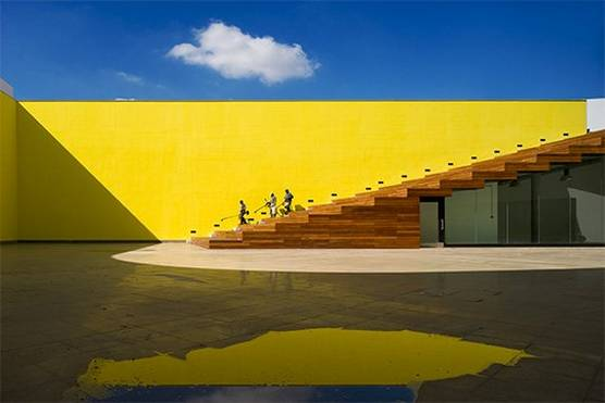 A bright yellow wall with brown stairs leading into a sunny courtyard, with glass doors beneath the stairs. Photo by Fernando Guerra with a Canon TS-E17mm f/4L lens.