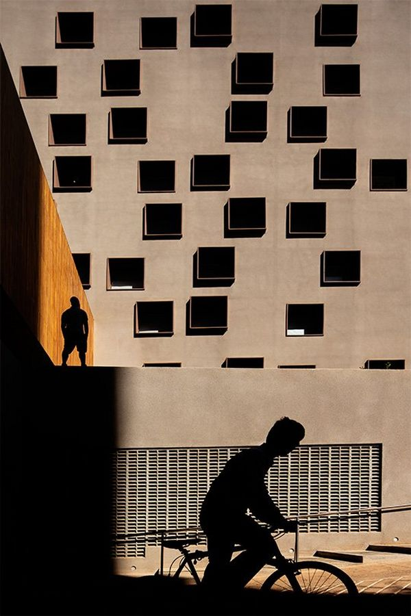 A silhouette of a cyclist passing a large concrete building with many windows. Photo by Fernando Guerra with a Canon TS-E 50mm f/2.8L MACRO lens.