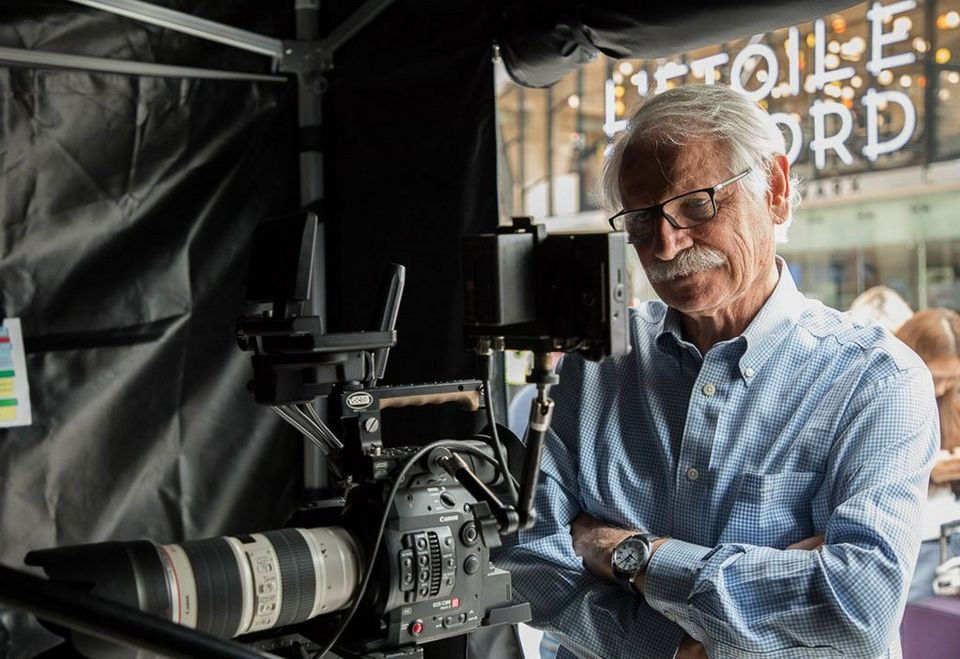 Yann Arthus-Betrand looks at a monitor by a video camera.