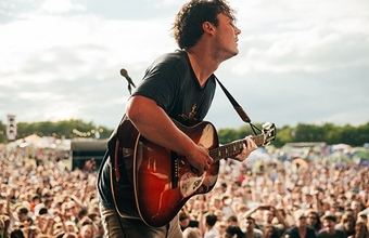 A rock musician on stage at a festival plays the guitar. Photo by Ben Morse.