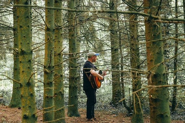 A guitarist practices among some trees. Photo by Ben Morse.