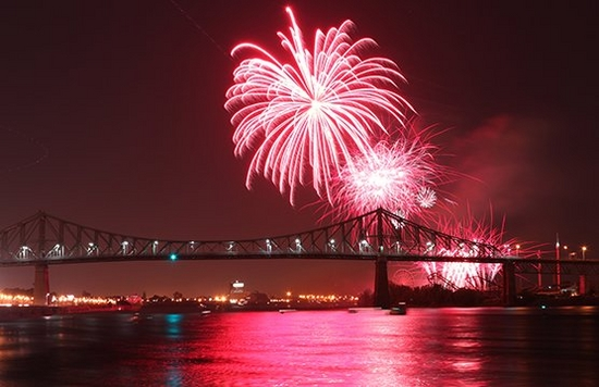 Pink fireworks explode over a bridge, lighting up the water.