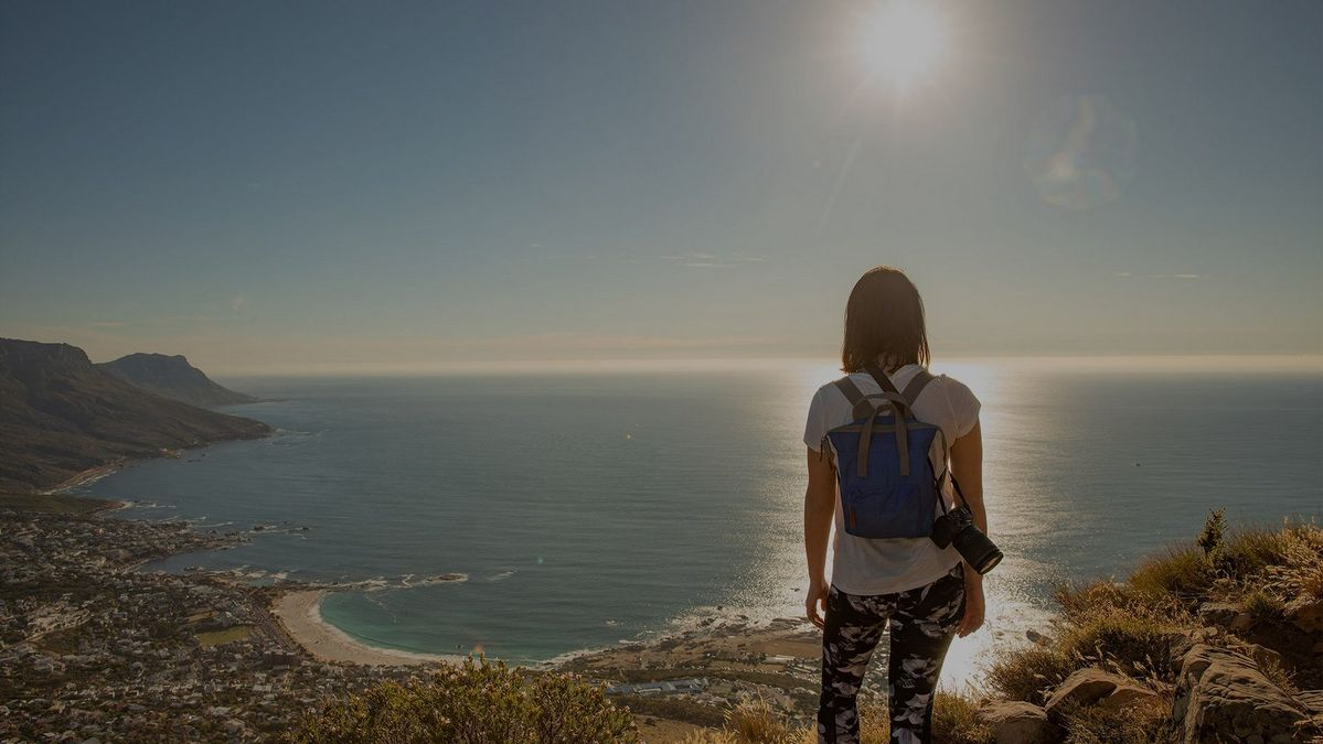 A casually-dressed woman, with a backpack and a Canon EOS RP camera over one shoulder, looks out to sea at a sunset.