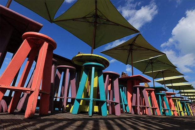 An array of colourful wooden stools, with square-shaped sunshades above, photographed from ground level looking up, on a Canon EOS 250D.
