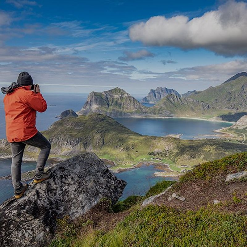 Photographer Richard Walch looks out over a coastline, taking a photo with his Canon camera.