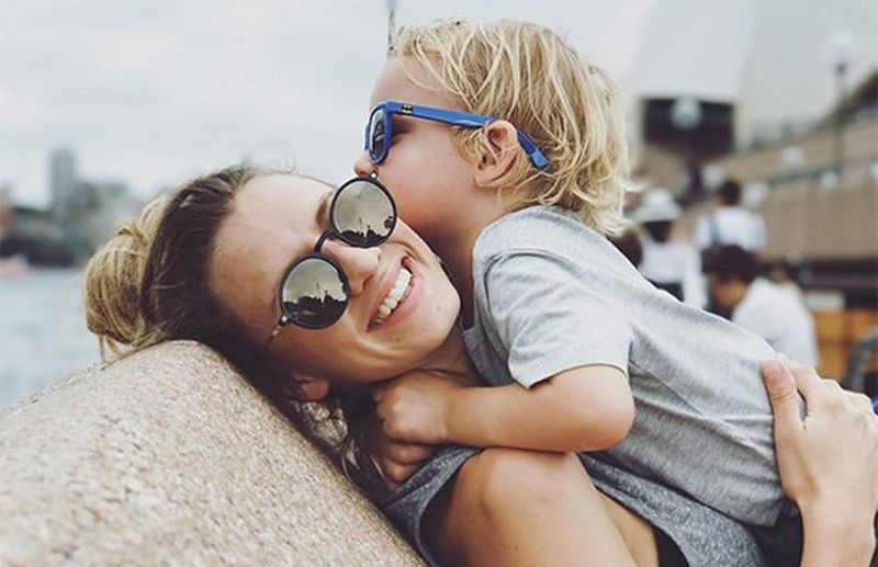 A mother picks her son up to hug, both of them wearing sunglasses. Photo by Christian Anderl.