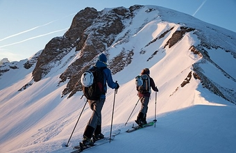 Two cross-country skiers travel along the narrow spine of a mountain, using their poles. Winter sports photo by Richard Watch.