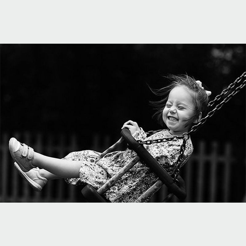 A smiling child playing on a swing. Photo by Helen Bartlett.