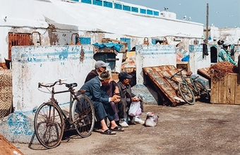 Fishermen in Essaouira, Morocco, sit by the harbour. Photo by Along Dusty Roads.
