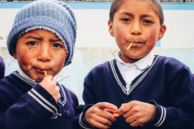 Young boys in Ecuador eating lollies. Photo by Along Dusty Roads.