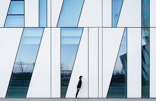 A person stands in front of a building with triangular windows larger than them, leaning diagonally. Photo by Daniel Rueda and Anna Devís.