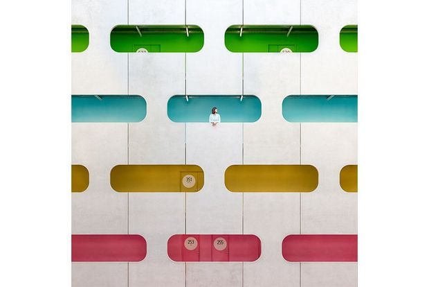 A woman leans out of a blue window in a multi-story atrium with colourful windows. Photo by Daniel Rueda and Anna Devís.