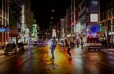 Two people skateboard down a city street at night, lights from buildings reflecting in the wet road surface.