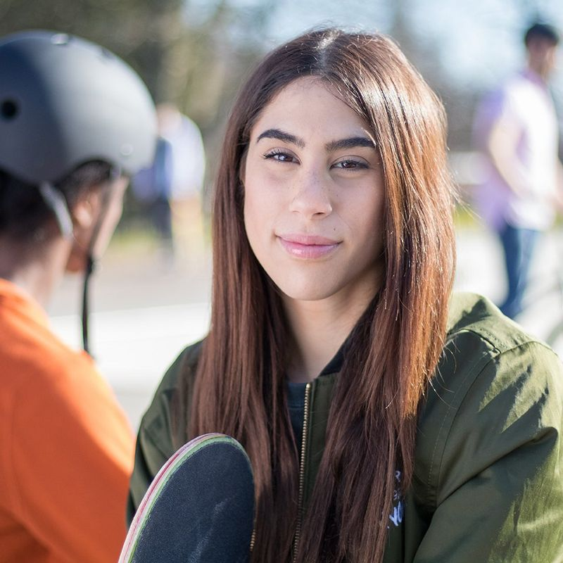 A portrait of a woman at a skate park.