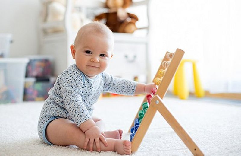 A baby plays with an abacus.