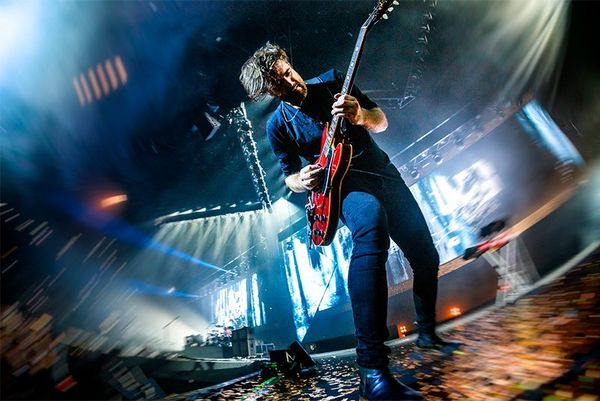 A low-angle, Fisheye lens shot of a guitarist on stage. Photo by Bart Heemskerk.