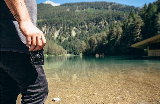 A man, shot from the shoulders down, stands by a lake holding a Canon PowerShot G5 X Mark II in his hand.