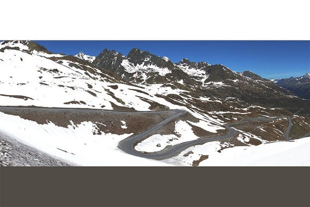 A panoramic shot of a winding road by snowy mountains.