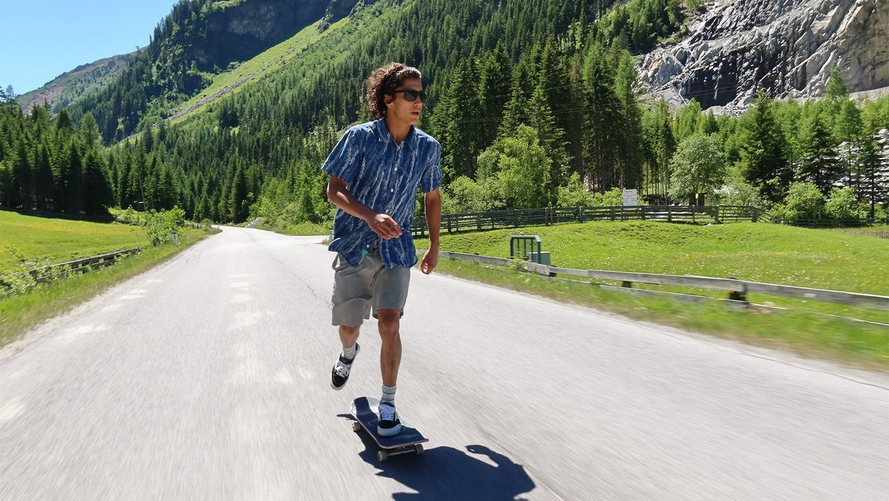 A man skateboards down a road past mountains covered in trees.