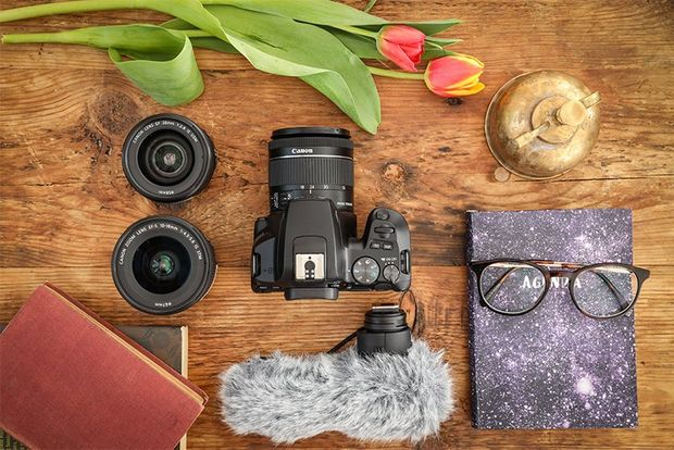 A flatlay of a vlogger's equipment, including the Canon EOS 250D.