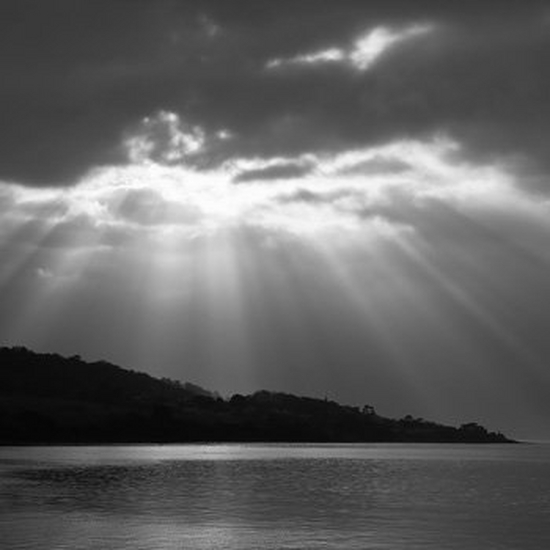 A black and white picture of a coastline with a burst of sunlight above.