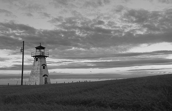 A black and white landscape shows a lighthouse.