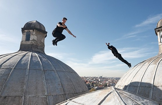 Two parkour athletes leap between domed rooftops in Istanbul.