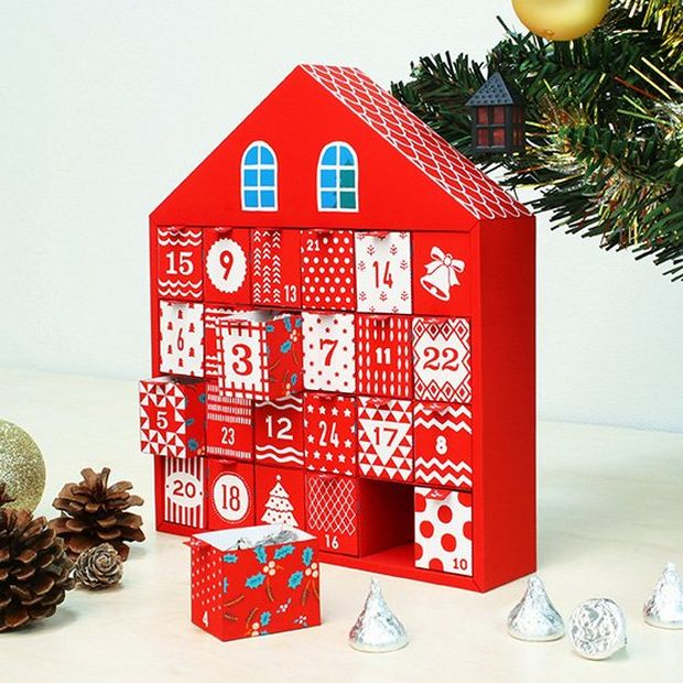 A homemade advent calendar shaped like a Christmas house.